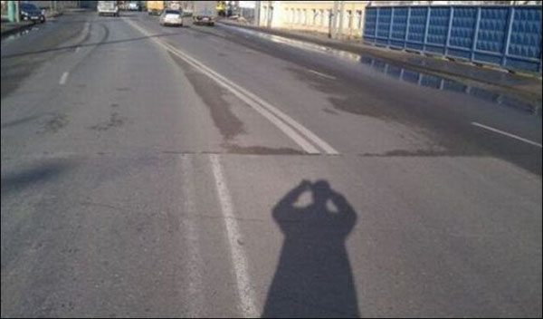 white road markings not lining up persons shadow taking photo
