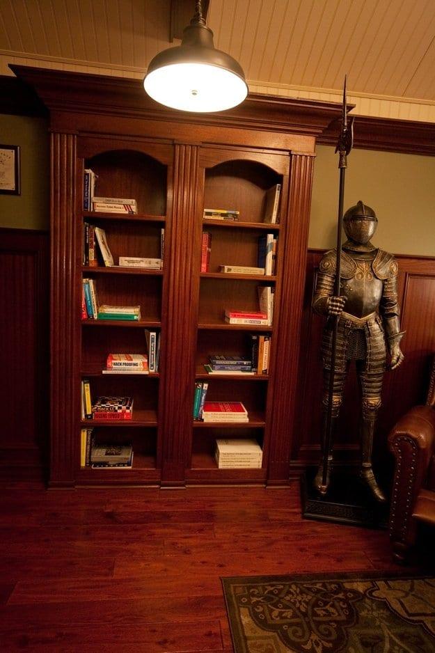 suit of armor standing next to bookshelf