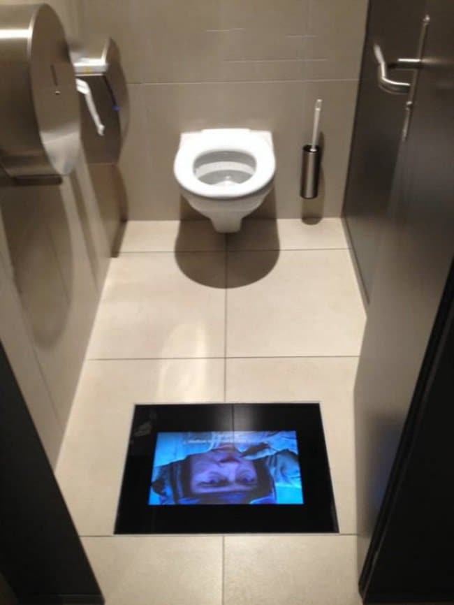 toilet with tv screen on the floor showing movie