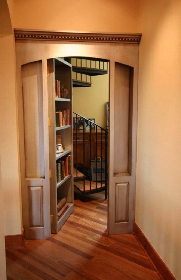 secret shelf door opened showing hidden spiral staircase