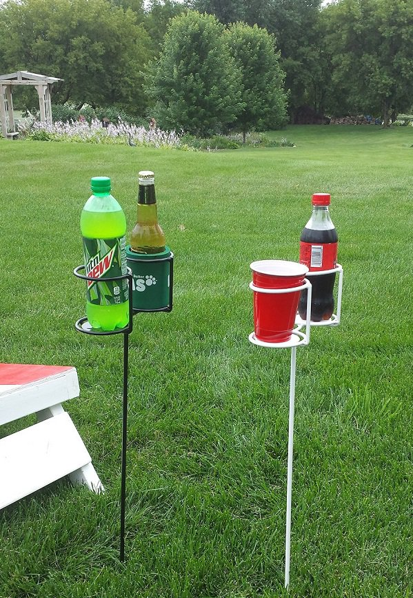 outdoor stakes in the ground holding drinks bottle and cup