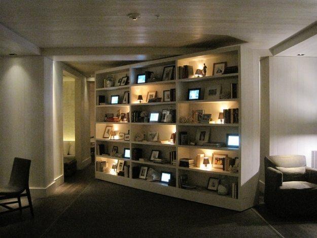 huge shelves covered in frames cracked open leading to hidden area