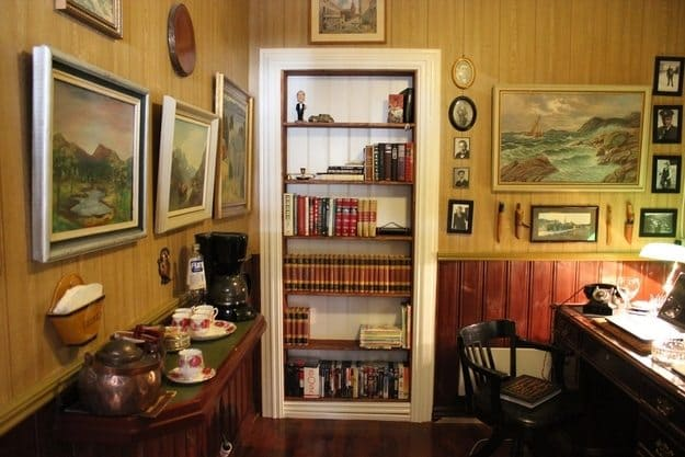 room with book shelves picture frames and desk