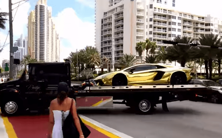 gold lamborghini loaded on the back of a truck