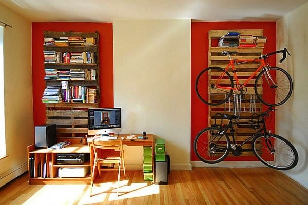 room with desk shelves books and bikes wood pallet shelves
