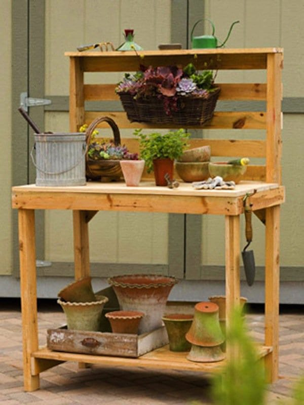 wood pallet garden bench storage with pots and plants and watering can