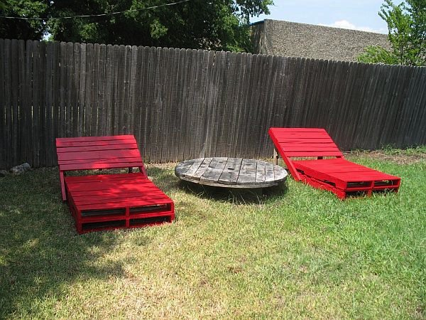 red outdoor loungers made of wood pallets with circular table