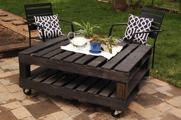 dark wood pallet outdoor table with wheels and two chairs