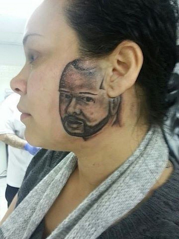 mans face on woman tattoo