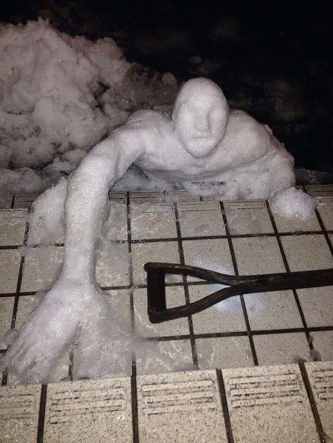 snowman reaching for shovel