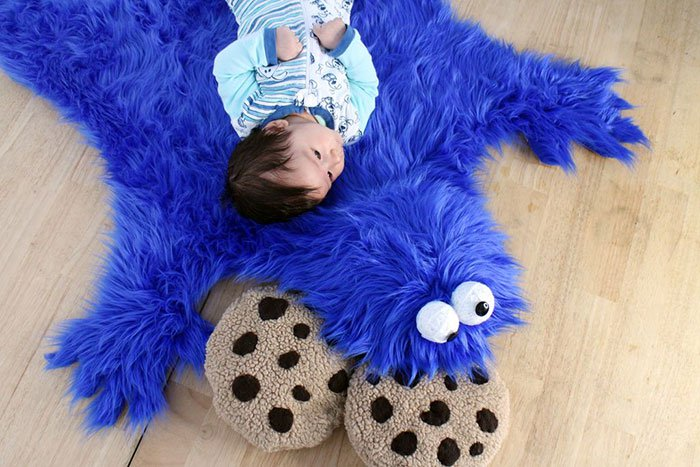 baby lying on cookie monster rug