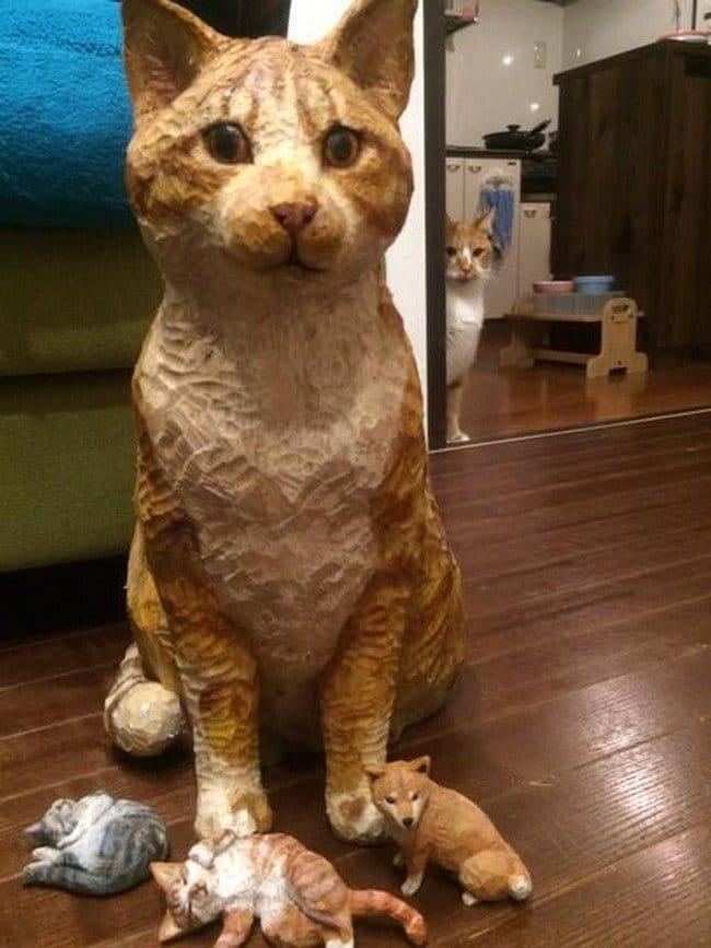 cat watching cat sculptures