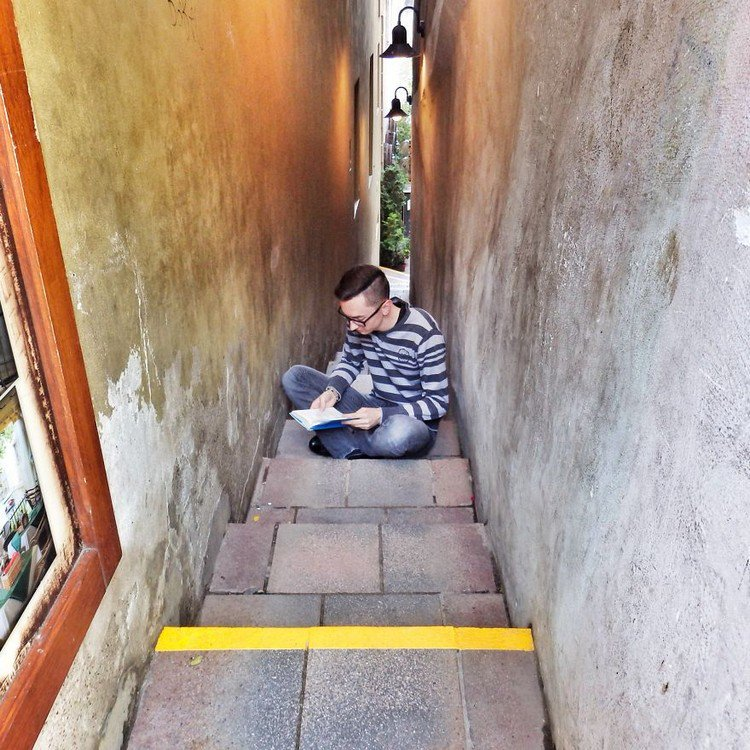 man reading stairs alley