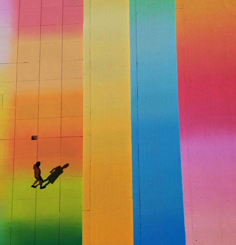 man walking colorful pool