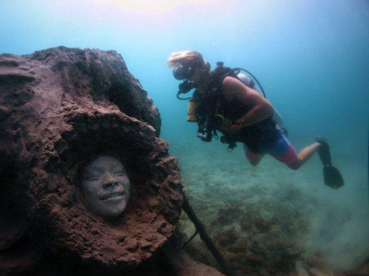 underwater sculpture smiling face diver