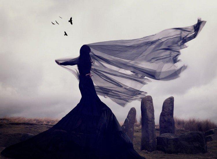 woman black veil ravens stones