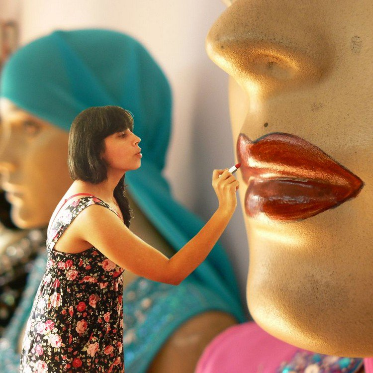 tiny woman painting mannequin lips