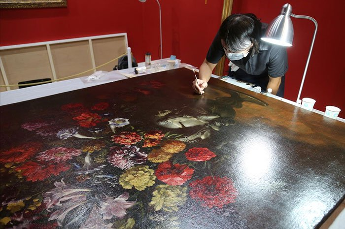 man restoring painting