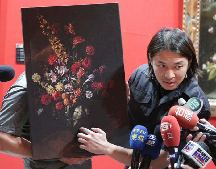 man talking to reporters about painting