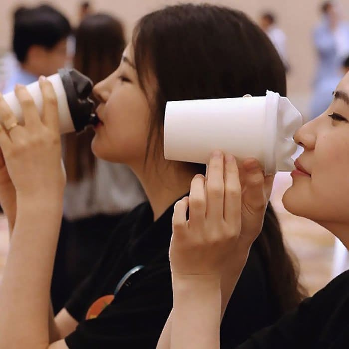 pair girls face coffee cups