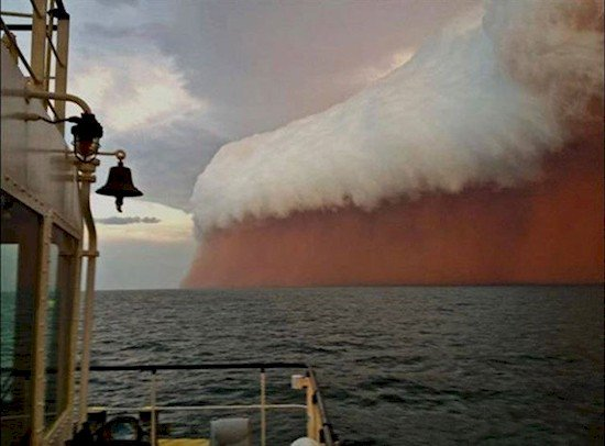 red sand storm moving over ocean
