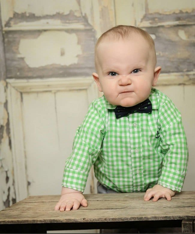 grumpy baby in checkered green shirt and bow tie