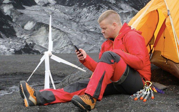 man charging phone wind turbine