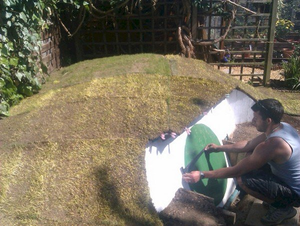 man grass roof hobbit hole