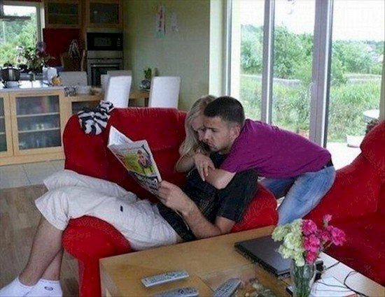 woman hugging man from behind whilst he sits crazy photos
