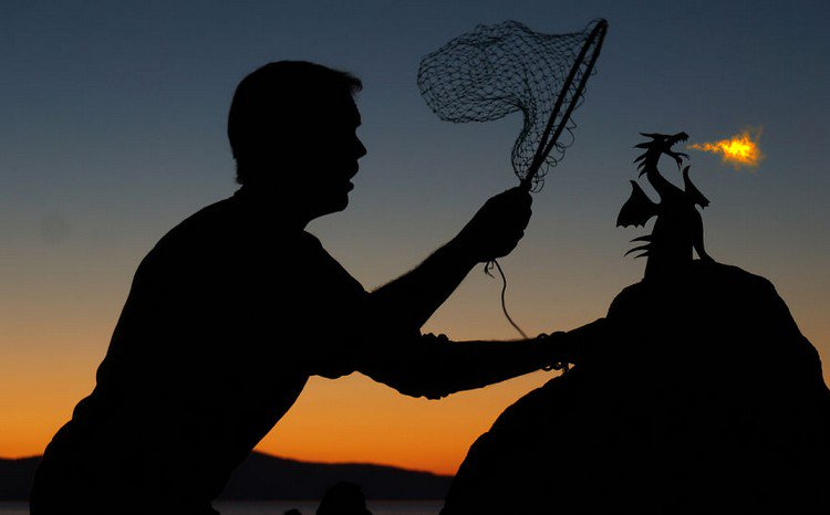 man catching rock dragon silhouette