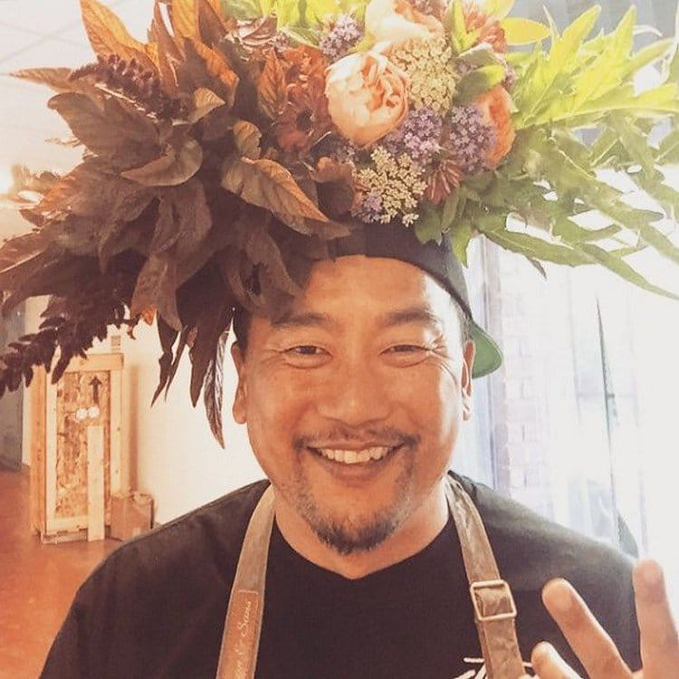 man hat flowers on head