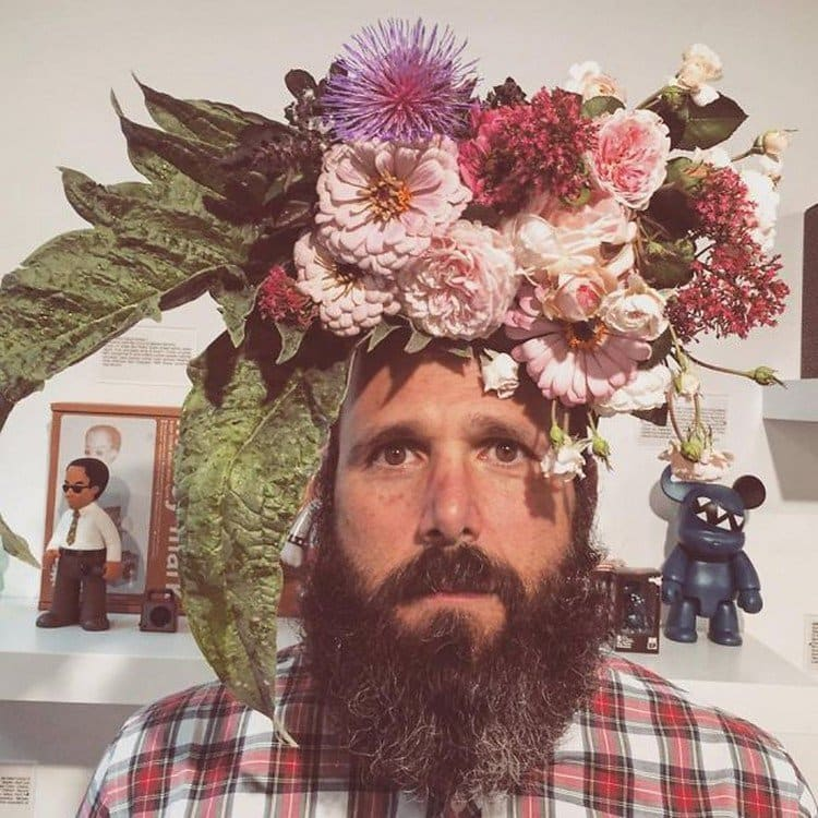 man with beard flowers on head