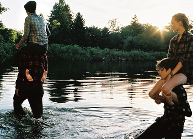 two couples walking through a lake sitting on eachothers shoulders with sunset and trees in background