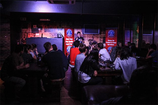 people looking at a stage for a comedy night