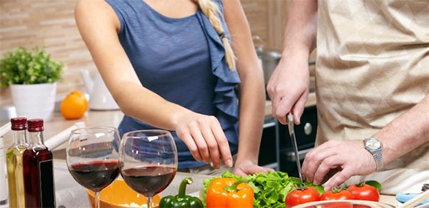 man and woman cooking with vegetables and wine