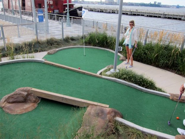 girl standing on a mini golf course with water and boat in background