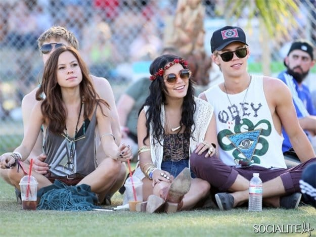 vanessa hudgens and friends sitting on grass with drinks at a festival