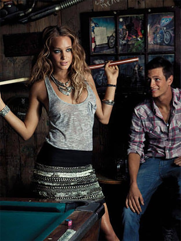 girl posing with a pool cue by a pool table with a man looking at her