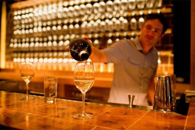 man pouring glass of wine at a bar