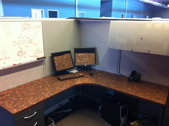 desk and computer screen and keyboard covered in pennies