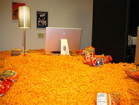 desk covered in thousands of cheetos with empty packets on top