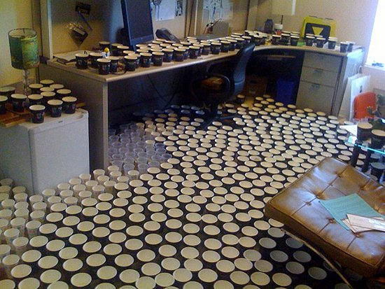 office filled with cups on floor and desk