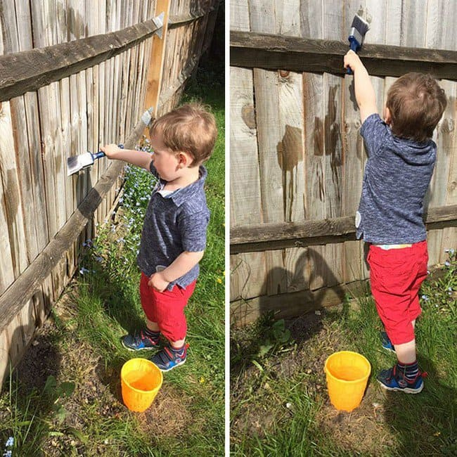 toddler painting fence