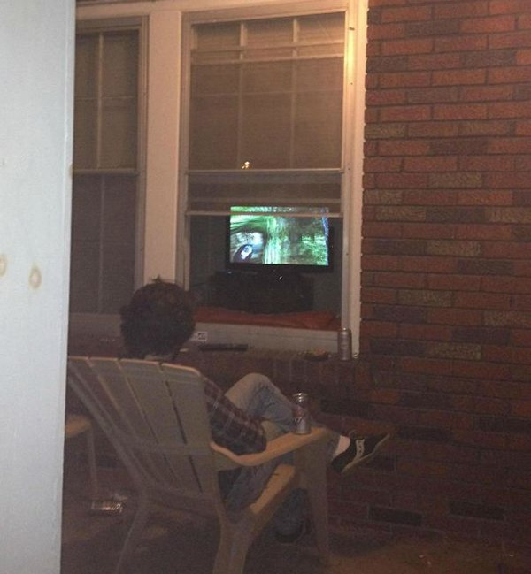husband watching tv outside looking through window
