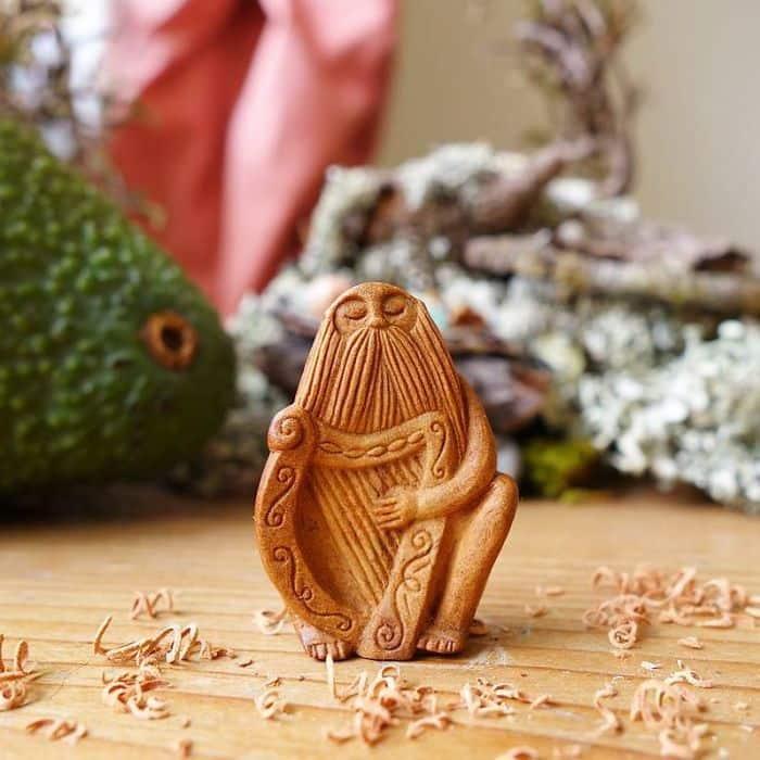 Artist Carves Avocado Pits beard creature with harp