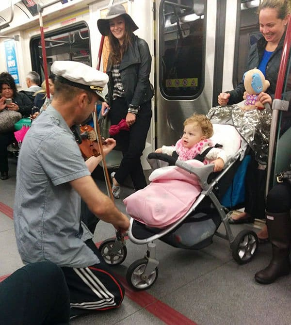 Weirdest People Ever Spotted On The Subway man playing violin to baby