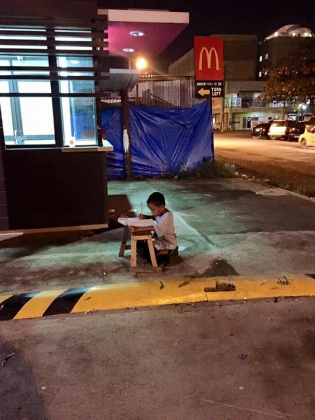 Strength Of The Human Spirit kid doing homework on the street