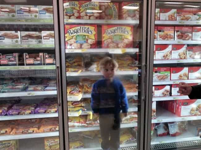 The Joys Of Shopping With Kids standing in freezer