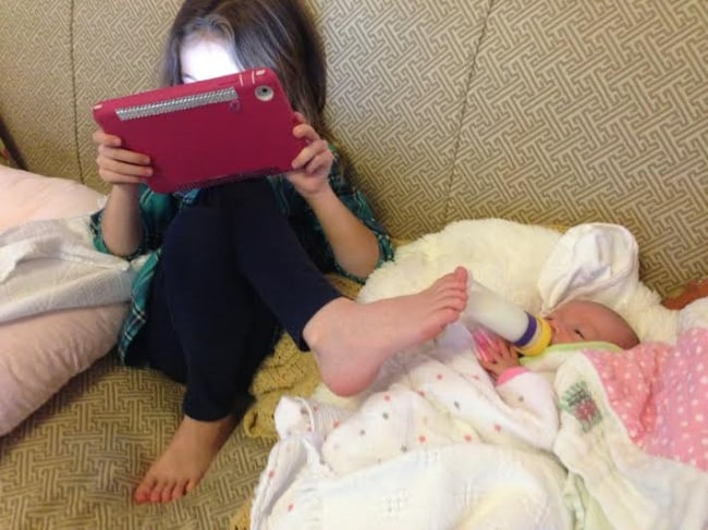 sister-feeding-baby