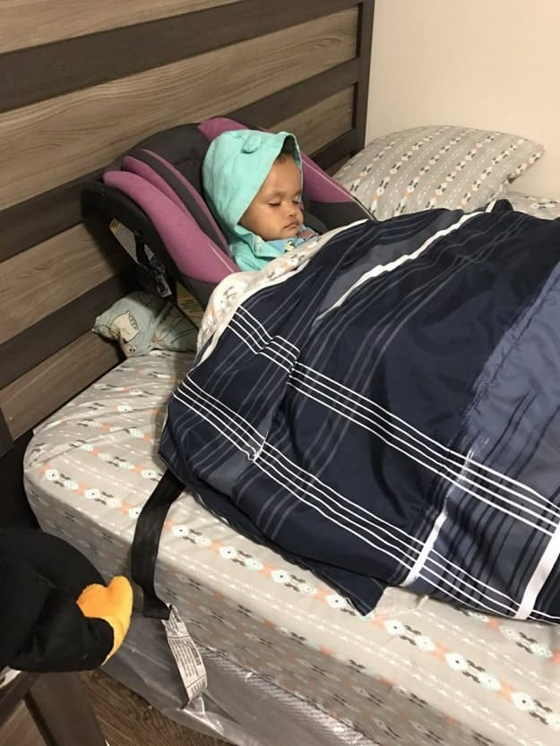 baby-girl-on-the-bed-sleeping-in-a-car-seat